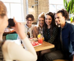 technology, lifestyle and people concept - happy friends with camera photographing at bar or cafe